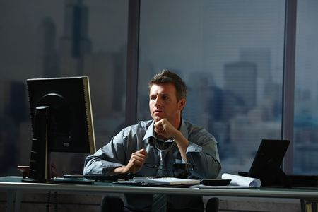 Tired businessman working late on computer in office holding glasses in hand. photo