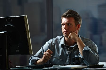 troubles: Tired businessman working late on computer in office holding glasses in hand. Stock Photo