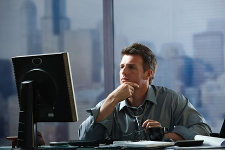 Tired businessman working late on computer in office holding glasses in hand. Stock Photo - 6397011