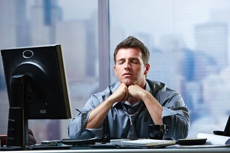 Exhausted businessman focusing on solution of problems sitting at office desk eyes closed. photo