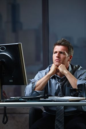 Determined businessman concentrating hard on difficult computer task working late in office looking worried. Stock Photo - 6396974