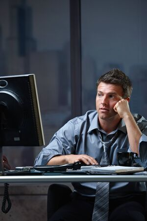 Tired professional businessman looking at computer screen troubled, thinking at office desk working overtime. photo