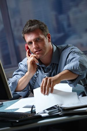 Mid-adult businessman speaking on landline phone working overtime in office checking papers. Stock Photo - 6397017