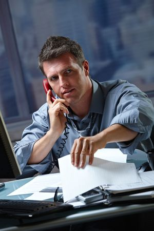 Mid-adult businessman speaking on landline phone working overtime in office checking papers. photo