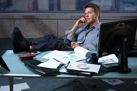 Tired businessman taking break speaking on landline phone with shoes off feet up on office desk holding glasses. photo