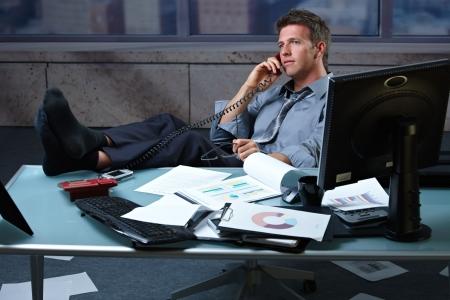 loosen up: Tired businessman taking break speaking on landline phone with shoes off feet up on office desk holding glasses. Stock Photo