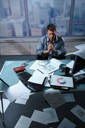 high angle: Tired businessman calling from office papers lying all around, picture taken from high angle.