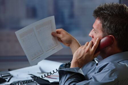 Mid-adult businessman talking on landline phone looking at business documents handheld in closeup. photo