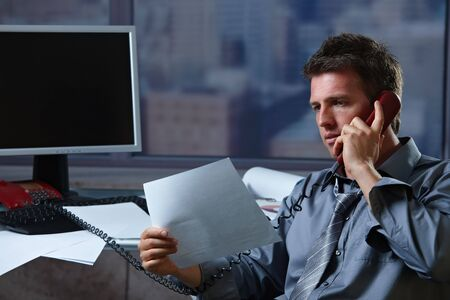 Mid-adult businessman talking on landline phone looking at business documents handheld. Stock Photo - 6396969