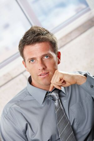 Portrait of confident businessman looking at camera with small smile leaning on chin. Stock Photo - 6397069