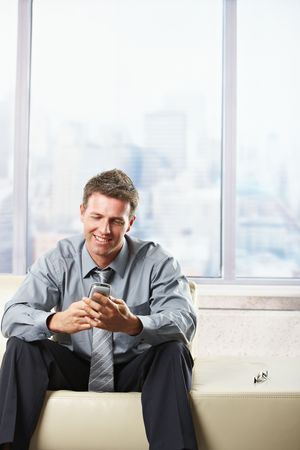 Mid-adult businessman looking down at mobile phone sitting on beige sofa in bright office. Stock Photo - 6396967