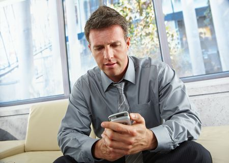 Mid-adult businessman looking down at mobile phone sitting on beige sofa in bright office. Stock Photo - 6397064