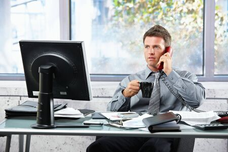 handheld computer: Mid-adult successful businessman calling on landline phone listening to conversation sitting at office desk with coffee mug in hand.