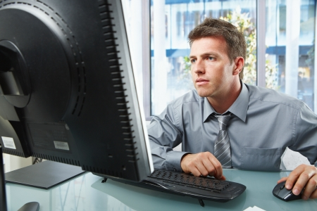 Elegant professional businessman working on computer looking at screen with hand on mouse in sunlit office.  photo