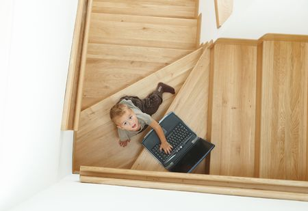 Little boy sitting on stairs, playing with laptop computer. Overhead shot. photo
