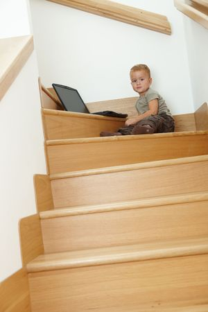 Little boy sitting on stairs, playing with laptop computer. photo