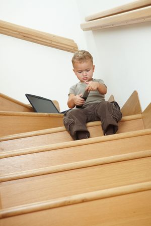 Little boy sitting on stairs, playing with remote control. photo