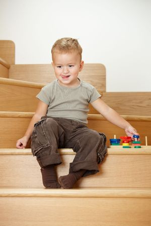 Happy little boy sitting on stairs, playing with colorful wooden toys. photo