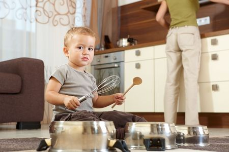 children cooking: Little boy sitting on carpet in kitchen playing with cooking pots, mother preparing food in background. Stock Photo