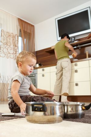 Little boy sitting on carpet in kitchen playing with cooking pots, mother preparing food in background. Stock Photo - 6401238