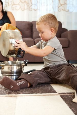 Little boy sitting on carpet in kitchen playing with cooking pots, mother sitting on sofa in background. photo