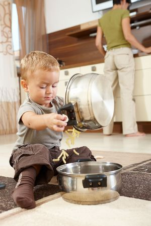 Little boy sitting on carpet in kitchen playing with cooking pots, mother preparing food in background. photo