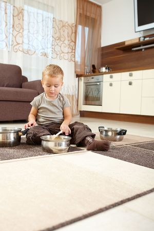 Little boy sitting on carpet in kitchen playing with cooking pots. photo