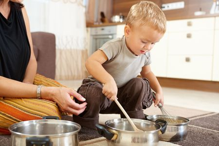 Little boy and mother sitting on carpet in kitchen playing with cooking pots. photo