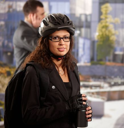 Portrait of young businesswoman wearing bike helmet, going to work, smiling. photo