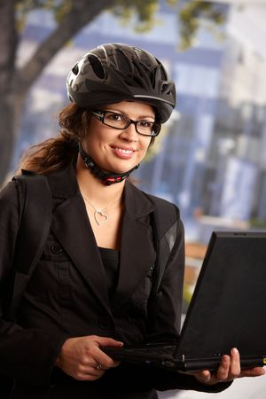 Portrait of young businesswoman wearing bike helmet, using laptop computer outdoor, smiling. photo