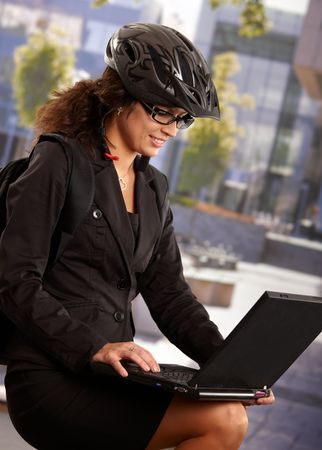 Portrait of young businesswoman wearing bike helmet, using laptop computer outdoor. photo