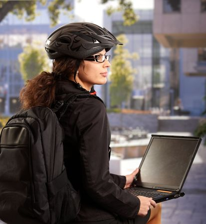 Portrait of young businesswoman wearing bike helmet, sitting in front of office building, using laptop computer. Stock Photo - 6401190