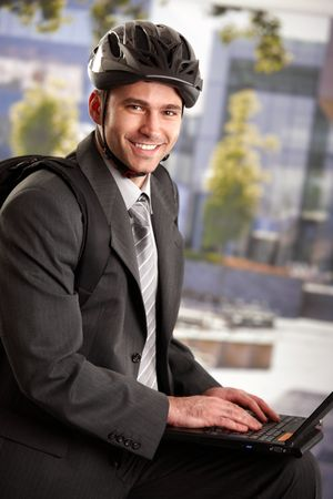 Portrait of young businessman wearing bike helmet, sitting in front of office building, using laptop computer. photo