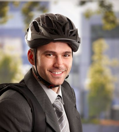 Portrait of young businessman wearing bike helmet, going to work, smiling. photo