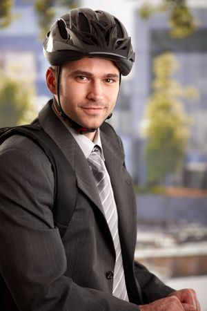 Portrait of young businessman wearing bike helmet, arriving to work at morning, smiling. photo