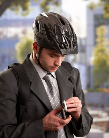 executive helmet: Portrait of young businessman wearing bike helmet, using mobile phone, outdoors.