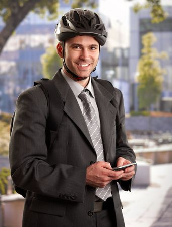 Portrait of young businessman wearing bike helmet, going to work, smiling. Stock Photo - 6401211