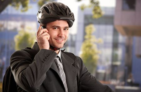 Portrait of young businessman wearing bike helmet, talking on mobile phone, outdoors. photo