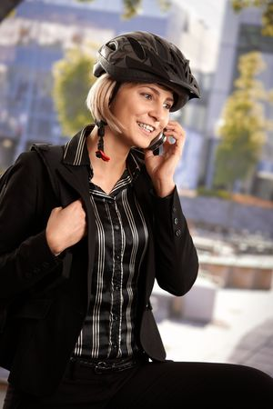 Portrait of young businesswoman wearing bike helmet, talking on mobile, outdoors. photo