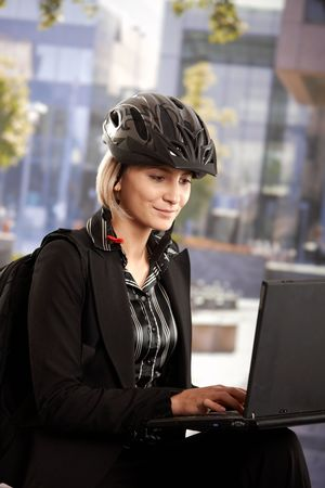 Portrait of young businesswoman wearing bike helmet, sitting in front of office building, using laptop computer. Stock Photo - 6401216