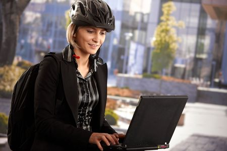 Portrait of young businesswoman wearing bike helmet, sitting in front of office building, using laptop computer. photo