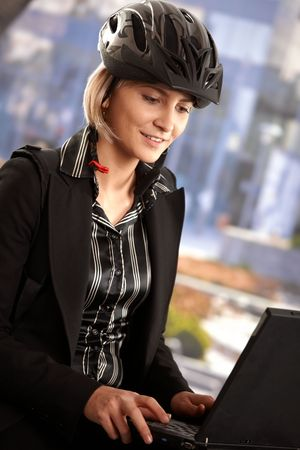 Portrait of young businesswoman wearing bike helmet, sitting in front of office building, using laptop computer. Stock Photo - 6401209
