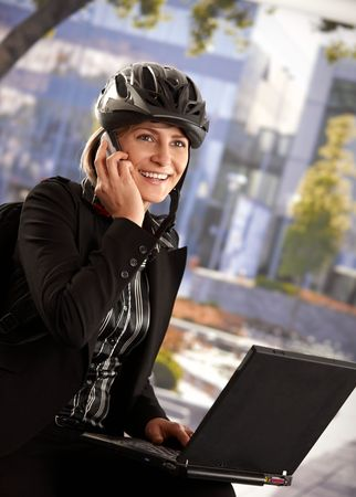Portrait of young businesswoman wearing bike helmet, sitting in front of office building, using laptop computer. Stock Photo - 6401227