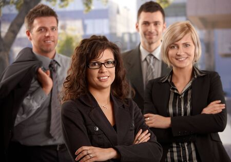 Portrait of young businesswoman standing outdoor with colleagues, smiling. photo