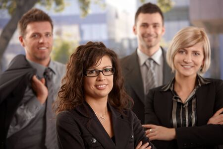 Portrait of young businesswoman standing outdoor with colleagues, smiling. Stock Photo - 6401204