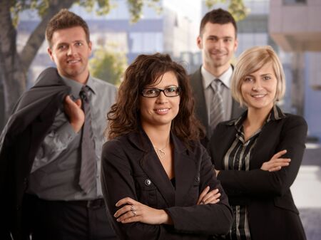 Portrait of young businesswoman standing outdoor with team smiling. photo
