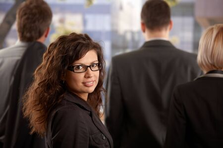Business people leaving office at afternoon young businesswoman standing outdoor, looking back, smiling. photo