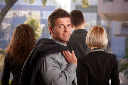 Business people leaving office at afternoon mid-adult businessman looking back, smiling. Stock Photo - 6401194