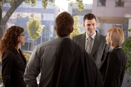 Group of young businesspeople talking in front of of office building. Stock Photo - 6401188