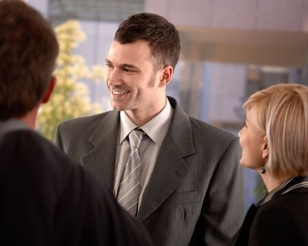 Portrait of young businessman standing outdoor talking with colleagues, smiling. photo